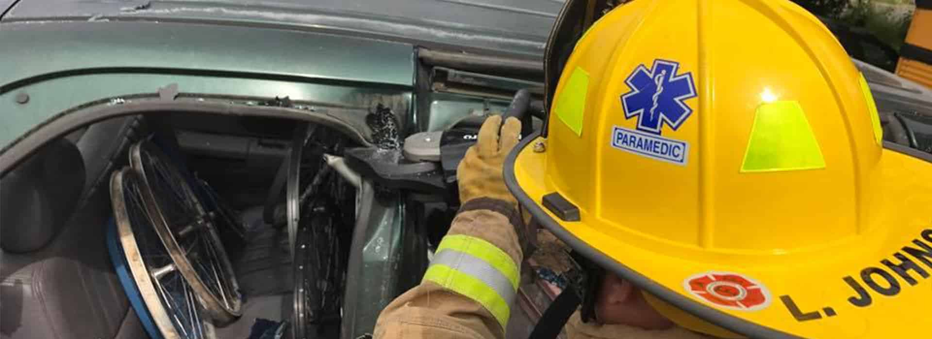A career Molalla firefighter uses a hydraulic tool to cut a vehicle.